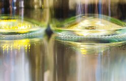 White wine bottles on glass table with bottles reflection Royalty Free Stock Photography