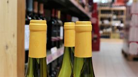 White wine in bottles in wine shop. Red and stock image