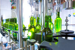 White wine in bottling machine at winery. White wine in glass bottling machine at winery Royalty Free Stock Photos