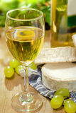 White wine, Brie and Camembert cheeses and grape. White wine, Brie, Camembert and grape on the wood surface, outdoor Royalty Free Stock Photo