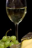 White wine and cheese. A glass of white wine and cheese on a black background Stock Image
