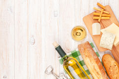 White wine, cheese and bread on white wooden table background Stock Image