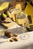 White wine with cheese and figs. White wine goblets with cheese, figs and nuts on cheeseboard on damask tablecloth Royalty Free Stock Images