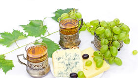 White wine, cheese and grapes on white table Stock Images
