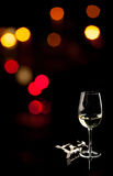 White wine. Glass with white wine on a black background with lights at night Royalty Free Stock Photos