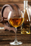 White wine glass with bottle and barrel on brown wooden background Royalty Free Stock Photos