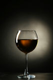 White wine glass with bottle on a black background Stock Photography