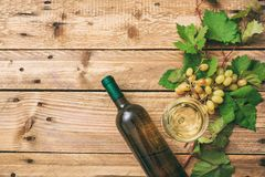 White wine glass and bottle and fresh grapes on wooden background, copy space stock photo