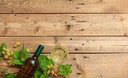White wine glass and bottle and fresh grapes on wooden background, copy space royalty free stock photos