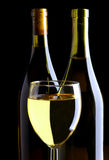 White Wine Glass and Bottles on Black Royalty Free Stock Photos