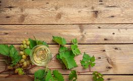 White wine glass and fresh grapes on wooden background, copy space royalty free stock photos