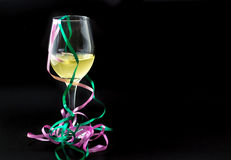 White wine in a glass with ribbons. Royalty Free Stock Image