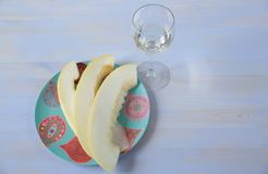White wine in a glass and ripe yellow sweet melon sliced in a plate with an ornament on a white blue background.