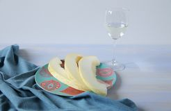 White wine in a glass and ripe yellow sweet melon sliced in a plate