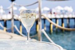 White wine glass on a sea background. White wine glass on a sea pier background royalty free stock photos