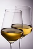White Wine Glasses. Overlaping on concentric white to gray background royalty free stock photography