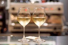White wine glasses in bar. Date time for two people inside restaurant or cafe Stock Photos
