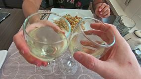 White wine glasses cheers. SLOW MOTION: two white wine glasses doing cheers with hands and celebrate in a restaurant, set table background and slow motion effect stock video footage