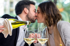 White wine glasses with couple in background. Stock Images