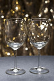 White wine glasses in front of glitter background Royalty Free Stock Images