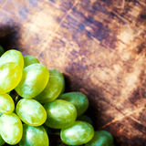 White  Wine grape bunch over wooden background. Green grapes mac Stock Photos