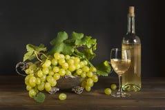 White wine, grape on silver basket. Bottle wine, glass wine on wood Stock Photos