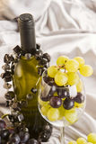White wine and grapes. A composition of white wine and grapes, on a silk silver cloth Stock Photo