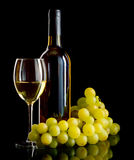 White wine and grapes. A bottle and a glass of white wine and a bunch of white grapes on black background Royalty Free Stock Photography