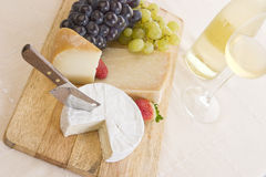 White wine, grapes and cheese. Composition of white wine, grapes, different cheeses with a cheese knife and two strawberries Royalty Free Stock Image