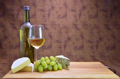 White wine, grapes and cheese. A bottle and glass of white wine with grapes two types of cheese Stock Photos