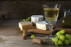 White wine, grapes and cheese on rustic dark wood Royalty Free Stock Photos