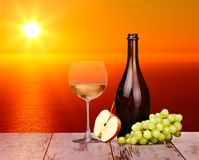 White wine grapes in a glass at sunset. On a piece of wood stock image