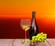 White wine grapes in a glass at sunset. On a piece of wood royalty free stock images