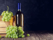 White wine and grapes. On table in front of stone wall with copy space. Toned Royalty Free Stock Photography