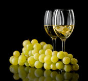 White wine and grapes. Two glasses of white wine and a bunch of grapes isolated on black Stock Photo
