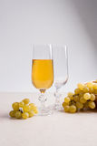 White wine and grapes. White wine in glass and grapes on light m Stock Photo