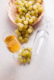 White wine and grapes. White wine in glass and grapes on light m Stock Photography