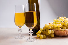 White wine and grapes. White wine in glasses, bottle of wine and Royalty Free Stock Images