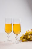 White wine and grapes. White wine in glasses and grapes on light Royalty Free Stock Image