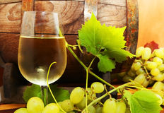 White wine with grapes and a wine barrel Stock Photography