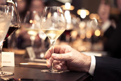 White wine on hand with dinner on restaurant Royalty Free Stock Photos
