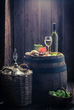 White wine and mix of cheese, grapes and demijohn with copy space. White wine and mix of cheese, grapes and demijohn on old wooden barrel with copy space Royalty Free Stock Image