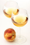 White wine and peach. Two glasses of white wine and peach on white background royalty free stock image