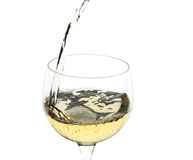 White wine pour. White wine being poured into a glass over white Royalty Free Stock Photography
