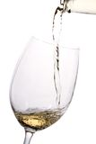 White wine poured into a glass. White wine pouring down from a wine bottle Royalty Free Stock Images