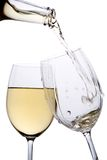 White wine poured into a glass. White wine pouring down from a wine bottle Royalty Free Stock Image