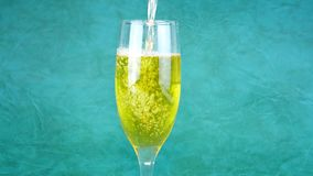 White wine is poured into a glass goblet.