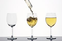 White wine pouring. Three wineglasses - empty, being poured and full Royalty Free Stock Photography