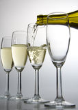 White wine pouring from bottle. Into one of four wineglasses on white background Royalty Free Stock Photo