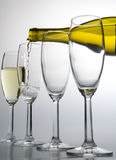 White wine pouring from bottle into wineglass. On white background Stock Images